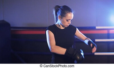 girl puts on boxing gloves on fists - Young woman in gym...