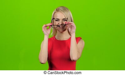 Girl puts on glasses with black rim, green screen studio