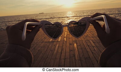 Girl puts on vintage heart-shaped sunglasses on the camera...