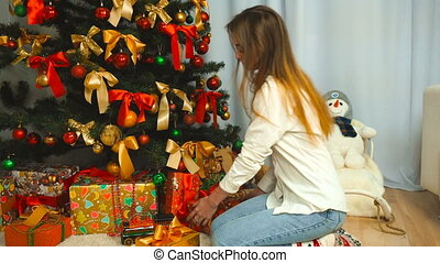 girl puts presents under the Christmas tree