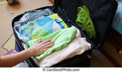girl puts things in the suitcase for travel in closeup