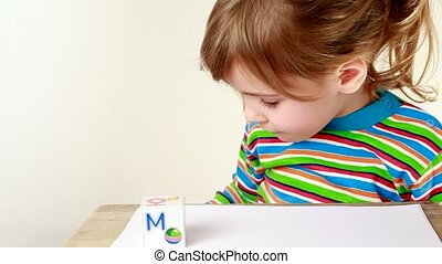 Girl puts together cubes with letters for obtaining word Mama