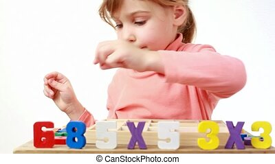 girl puts wooden figures on a table, where box with cells is