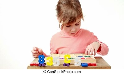 girl puts wooden multicolor figures in box with a cells