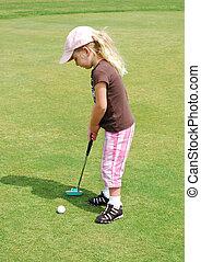 child putting golf ball