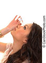 Girl putting eye drops.