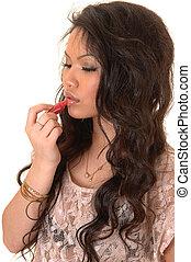 Girl putting lipstick.