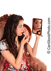Girl putting lipstick on.