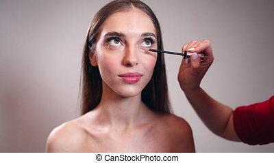 Girl Putting Mascara on Eyelashes - Young girl isolated on...