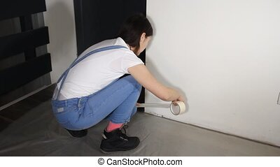girl putting masking tape - young woman doing renovations at...