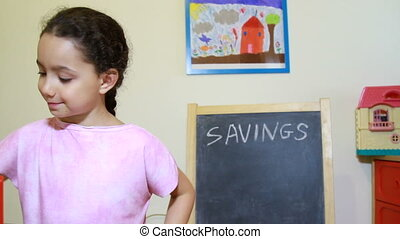 Girl putting money into savings box - putting money in penny...