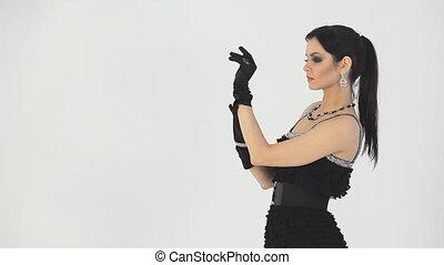 Girl putting on gloves. White