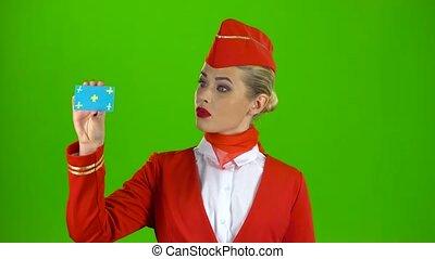 Girl raises a card and shows okey. Green screen - Stewardess...