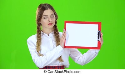 Girl raises a red tablet with paper . Green screen