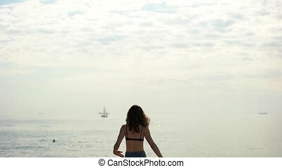 Girl raising hands at the sea
