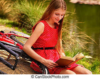 Girl read book near bicycle on river beach. - Girl wearing ...