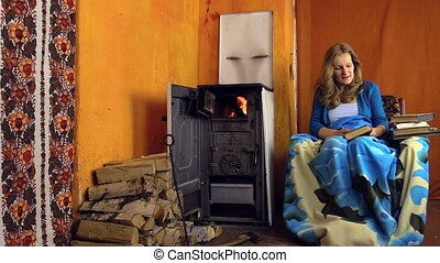 girl read book near stove - young girl found an interesting...