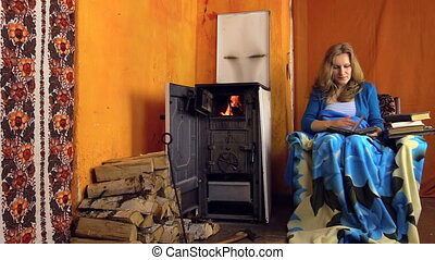 girl read book room stove - girl sit in armchair near the...