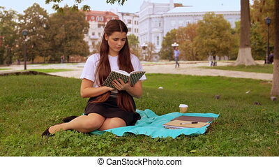 girl read poem in park - caucasian student reading book...