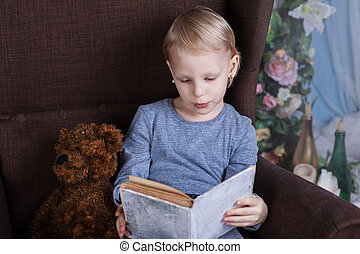 Girl reading a book in a chair