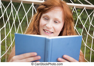 Girl reading a book in the garden