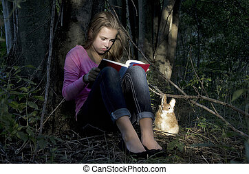 girl reading a book in woods