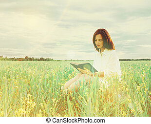 Girl reading a book on summer wildflower meadow