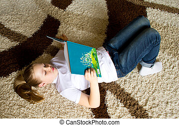 girl reading a book on the carpet