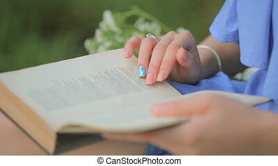 girl reading a book outdoors, close-up