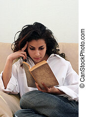 Girl reading a book - Teenage indian girl reading a book on...