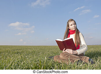 Girl reading a book sitting at grass