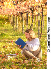 Girl reading a book sitting in the nature