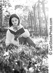 Girl reading a book sitting in the nature with a fallen leaf in her hand