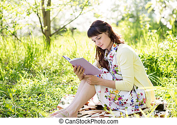 girl reading a book sitting on grass