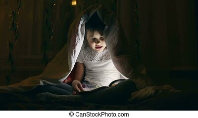 girl reading a book with a flashlight under the covers at night