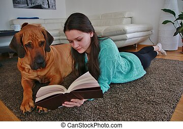 Girl reading a book with big brasilian mastiff