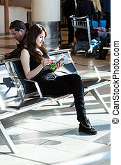 girl reading a magazine in the waiting room of the airport. S