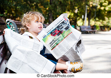 Girl reading a newspaper.