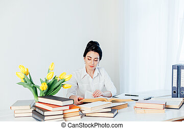 girl reading book at the table in the Office business