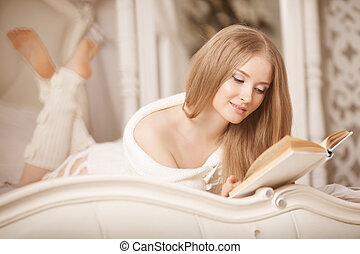 Girl reading book. Beautiful young woman lying on the sofa reading a book in the bedroom.