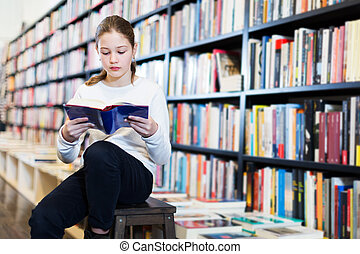 Girl reading book in bookshop