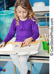 Girl Reading Book In Classroom