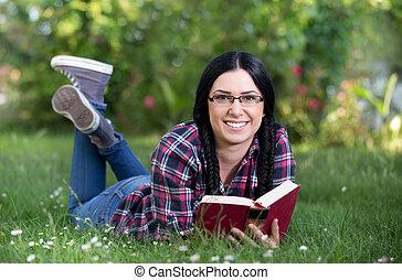 Girl reading book in park