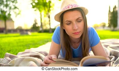 Girl reading book lying down on a blanket in the park at sunset
