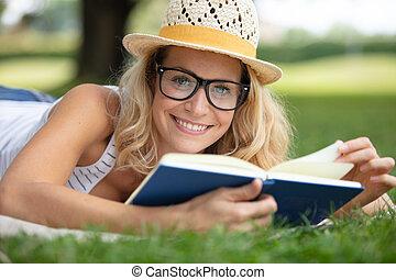 girl reading book lying in warm summer grass