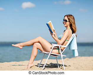 girl reading book on the beach chair - summer holidays and...
