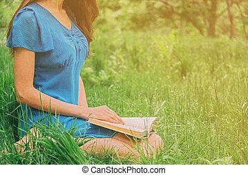 Girl reading book outdoor in summer
