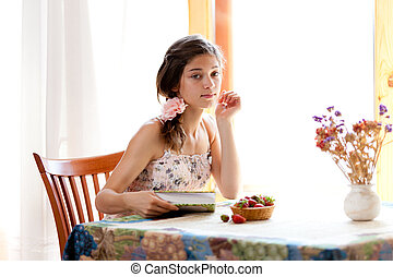 Girl reading book sitting at table indoor in summer day with str