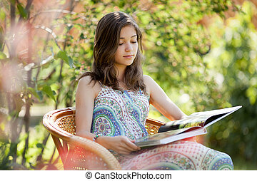 Girl reading book sitting in wicker chair outdoor in summer ...