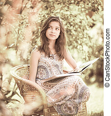 Girl reading book sitting outdoor in summer day. Retro stylized photo.